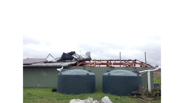 Strong winds removes half of this barn roof and solar panels, and flipping a horse a trailer on its side._422563