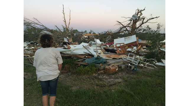 Woman surveys tornado damage to house (KXAN photo_David Yeomans)_463195
